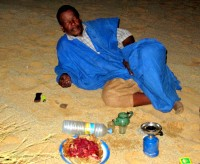 Mahmoud relaxes after a long battle with the Sahara (note propane burner, tea kettle, and raw camel meat!), Ben Amira, Mauritania, Africa